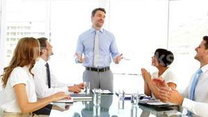 Businessman receiving praise from his employees at meeting