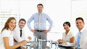 Businessman receiving praise from his staff at meeting and giving thumbs up