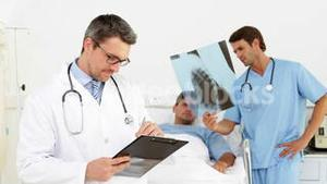 Doctor checking sick patients chart while surgeon looks at xray