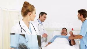 Doctors speaking with sick patient in bed while one checks xray