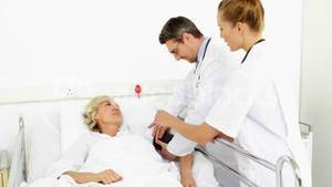 Doctors taking blood pressure of sick patient in bed