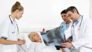 Doctors explaining xray to patient in bed