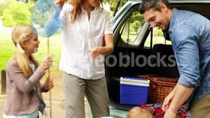 Family unloading their car for a camping trip