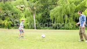Father and son kicking a football