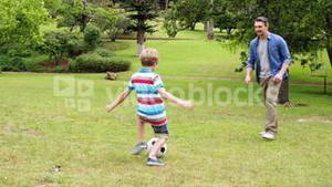 Father and son kicking a football back and forth