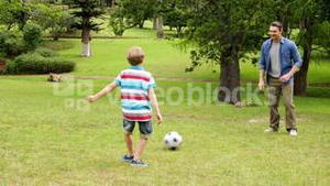 Father and son kicking a football back and forth in the park