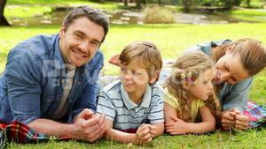 Cute family smiling at camera in the park