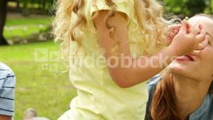 Cute girl putting flower behind her mothers ear