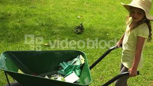 Cute girl pushing a wheelbarrow