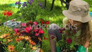 Cute girl holding a pot of flowers in the garden