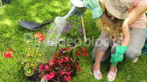 Cute little girl watering flowers with her mother