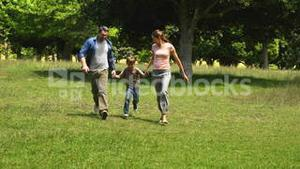 Little boy and parents running towards camera in the park holding hands