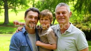 Three generations of men smiling at camera in the park
