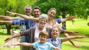 Multi generation family posing and smiling at camera in a park