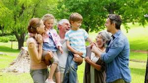 Multi generation family posing and laughing at camera in a park