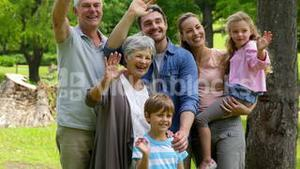 Multi generation family posing and waving at camera in a park