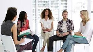 Cheerful psychologist leading group of people