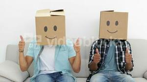 Silly employees with boxes on their heads giving thumbs up