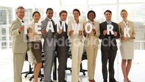 Happy business people holding letters spelling teamwork