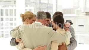 Business people hugging each other in a circle