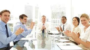Business people clapping at presentation at the camera