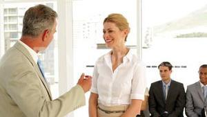 Businessman shaking the hand of job applicant and talking with her