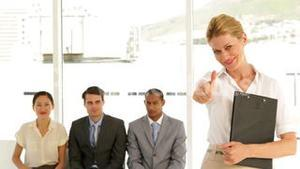 Businesswoman giving thumbs to camera in front of applicants