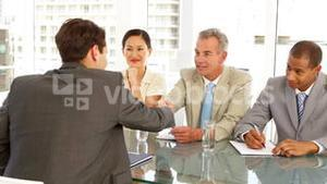 Businessman being interviewed by panel and being offered the job