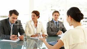 Businesswoman being interviewed by panel and being offered the job