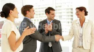Business people shaking hands at interview while others applaud
