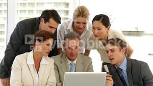 Positive business team discussing something on the laptop