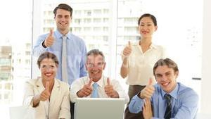 Happy business team posing in front of laptop