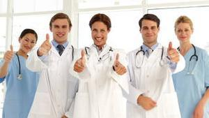 Confident medical team looking at camera and giving thumbs up