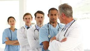 Medical team crossing arms and looking at each other
