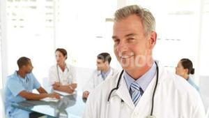 Happy doctor looking at camera and his staff behind him