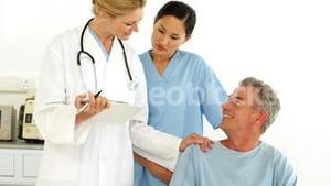 Friendly medical team talking with disabled patient