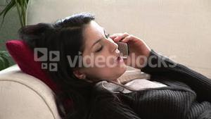 Woman on Sofa Talking on Telephone