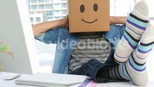 Photo editor wearing smiley face box on his head