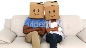 Team sitting on couch with emoticon boxes on their heads