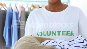 Pretty volunteer holding a clothes donation box
