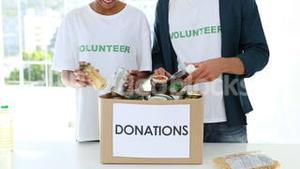 Happy volunteer team packing a food donation box