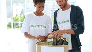 Young volunteer team packing a food donation box