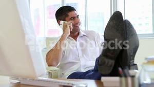 Businessman talking on the phone with feet up on desk