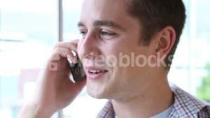 Casual businessman smiling and talking on phone