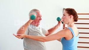 Older man lifting hand weights with the help of his physiotherapist