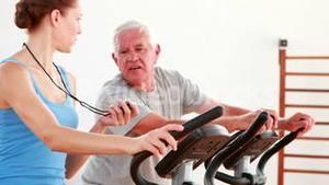 Elderly man using the exercise bike with his trainer