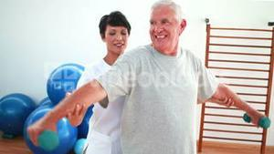 Happy physiotherapist helping elderly patient lift hand weights