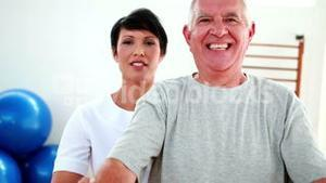 Smiling physiotherapist helping elderly patient lift hand weights