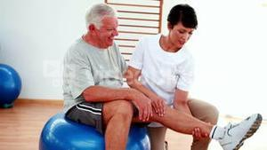 Smiling physiotherapist helping elderly patient bend knee