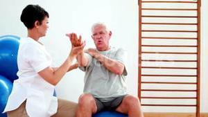 Smiling physiotherapist helping elderly patient stretch arm